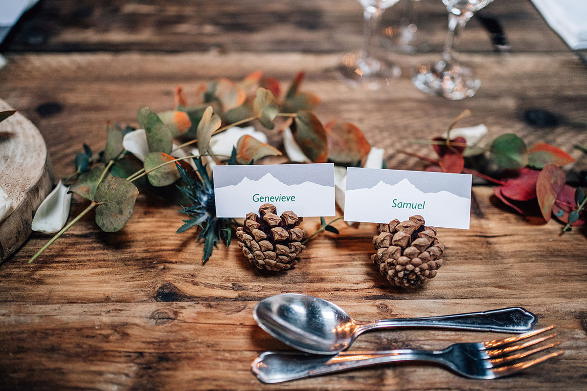 pine cone wedding place names with leaf decor on wooden tables