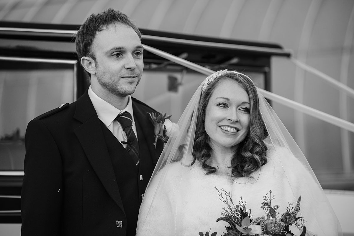 black and white image of bride and groom smiling next to MET wedding car