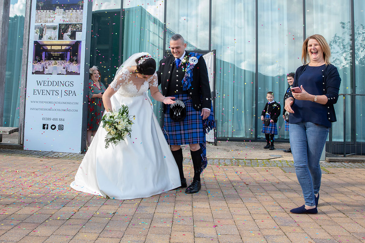 bride and groom showered in confetti with one guest outside The Shore Loch Lomond
