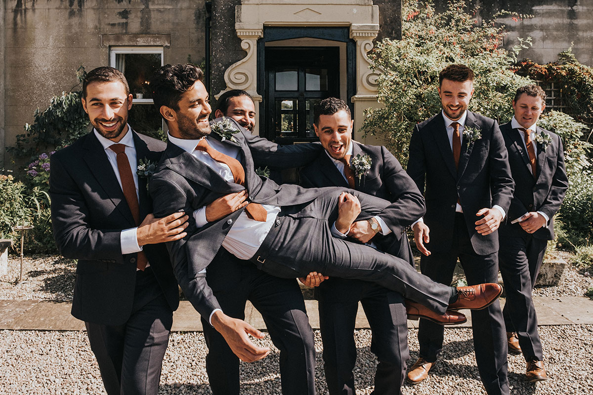 groom being carried by groomsmen and laughing outside Balinakill Country House in Kintyre