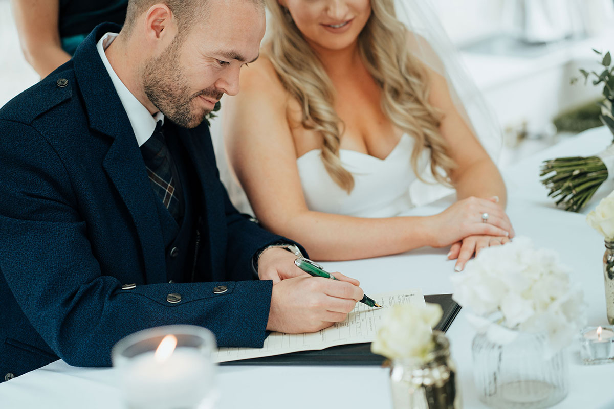 groom signing wedding register with black fountain pen