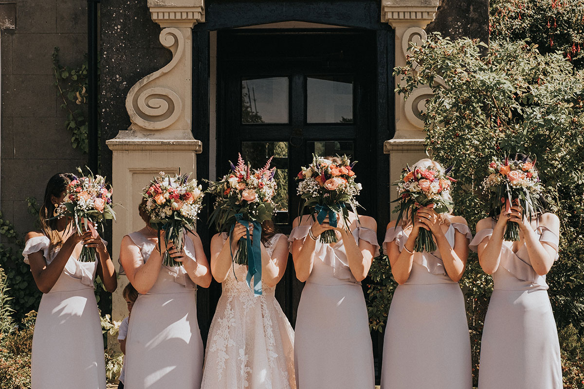 bride and 5 bridesmaids wearing lilac dresses holding bouquets up to face outside Balinakill Country House in Kintyre