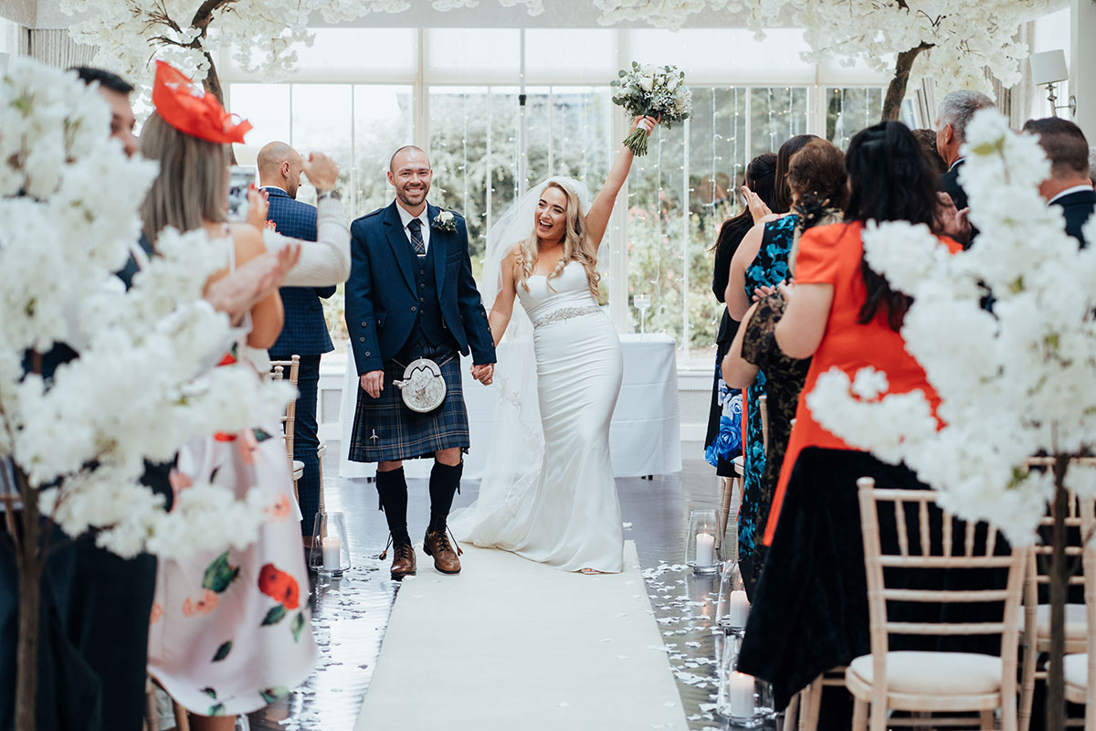 bride and groom walking up aisle and bride punching air with bouquet in hand