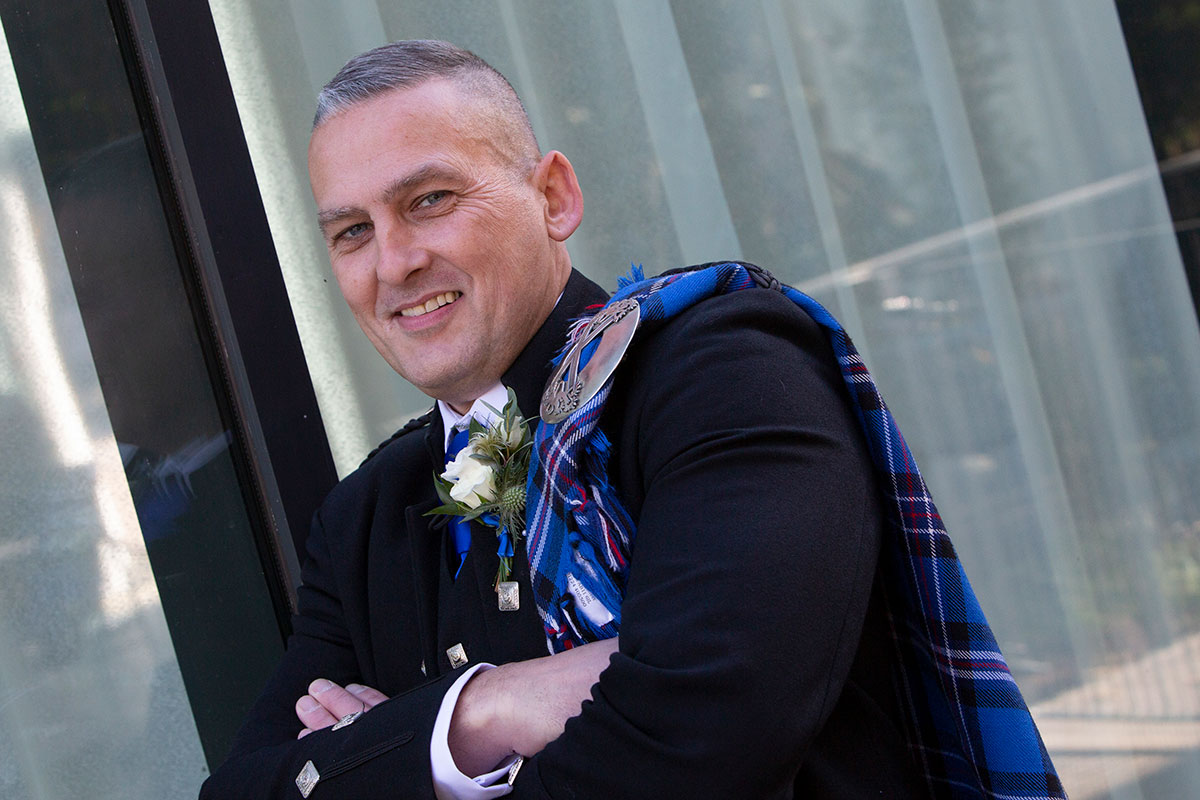 groom smiling wearing Rangers tartan fly plaid from McCalls