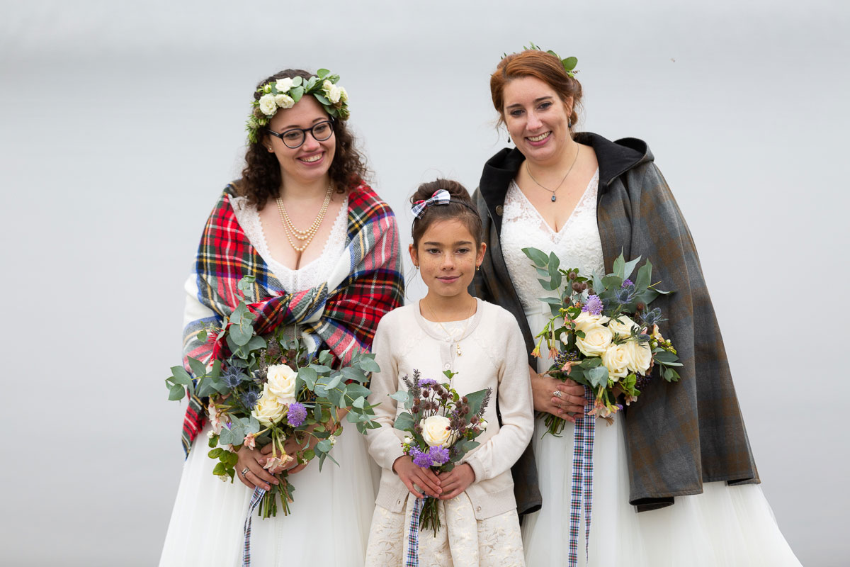 two brides wearing tartan shawl and cape pose with their daughter after wedding ceremony on shore of Loch Turret Reservoir in Perthshire