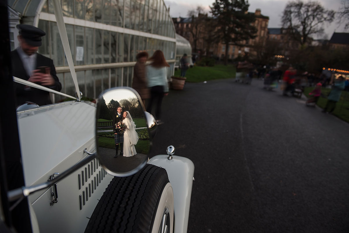 bride and groom photographed in mirror of wedding car outside Kibble Palace in Glasgow