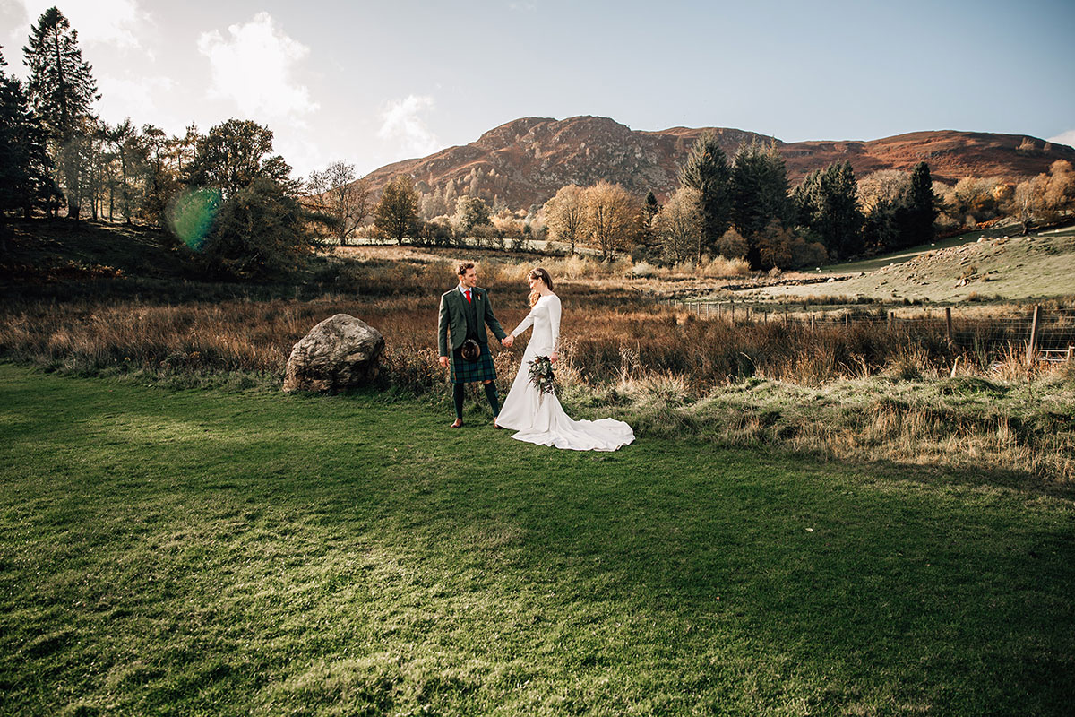 bride and groom walking in field at Cardney Steading with hills in background