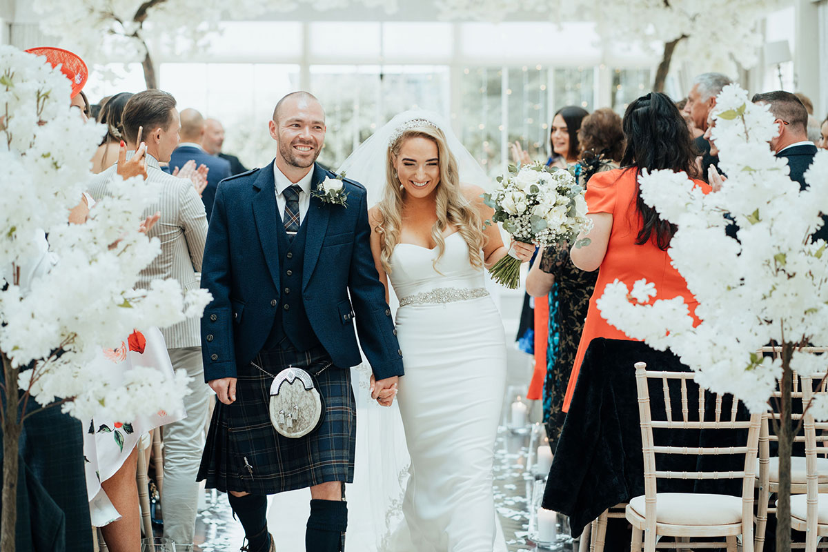 newlywed bride and groom walking up aisle at Carlowrie Castle