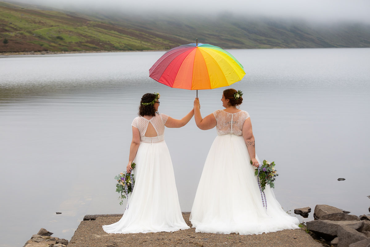 two brides with back to camera and holding rainbow umbrella on shore of Loch Turret Reservoir in Perthshire