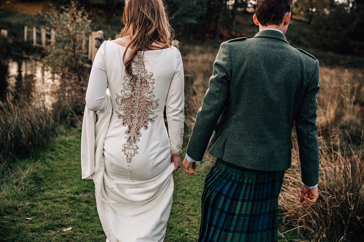 back of bride and groom as they walk towards a loch in autumn