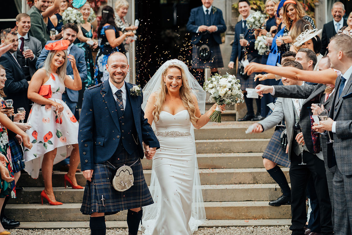 bride and groom outside Carlowrie Castle being showered by confetti thrown by guests