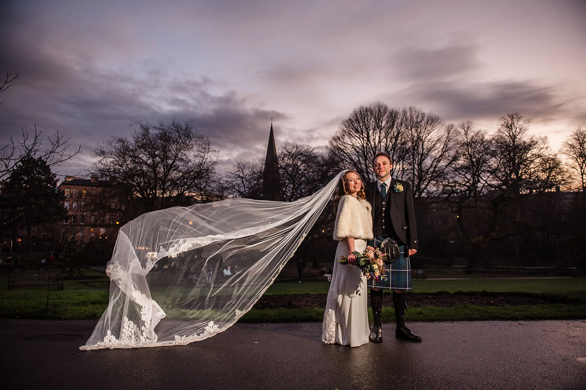 groom and bride with veil catching in breeze in Botanic Gardens in Glasgow