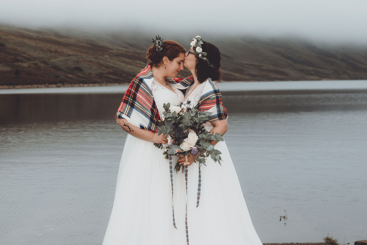 one bride kissing another bride's forehead on shore of Loch Turret Reservoir in Perthshire with misty mountains in background