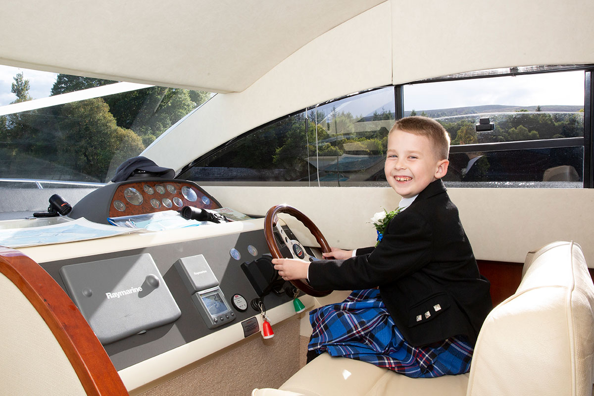 young boy sitting at steering wheel of Beau Jangles boat on Loch Lomond
