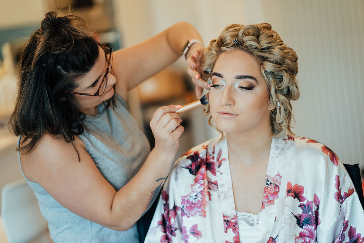 bride wearing floral robe getting makeup done on wedding morning