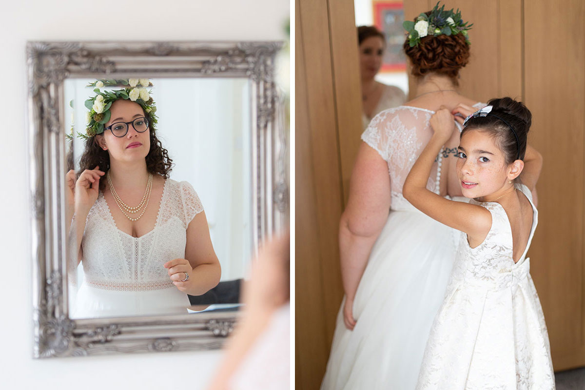 bride wearing glasses and floral crown looking in mirror and second bride and young girl getting ready on wedding morning