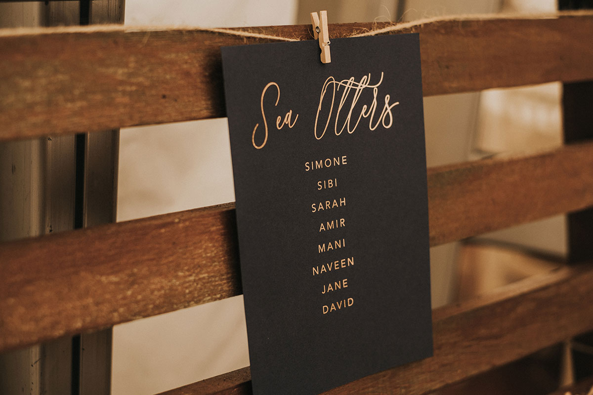 black and gold script Sea Otters table sign at wedding