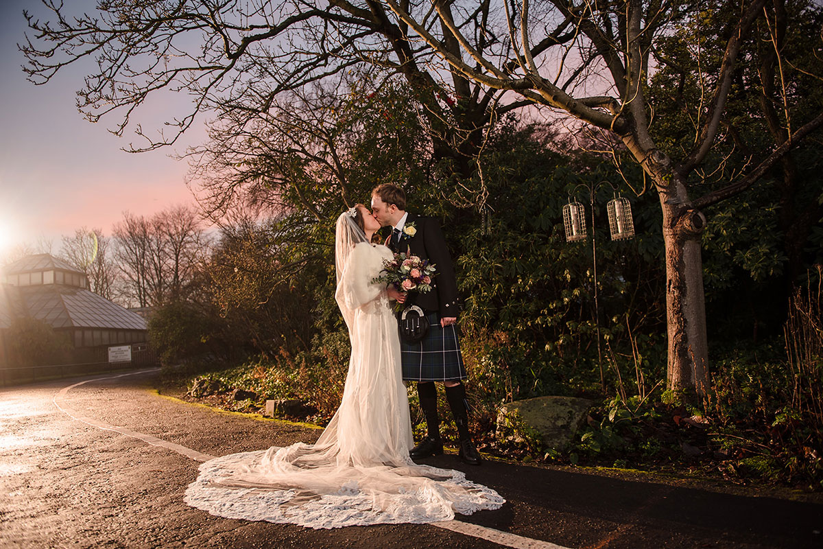 bride and groom kissing under tree and winter sun in sky at Botanic Gardens in Glasgow