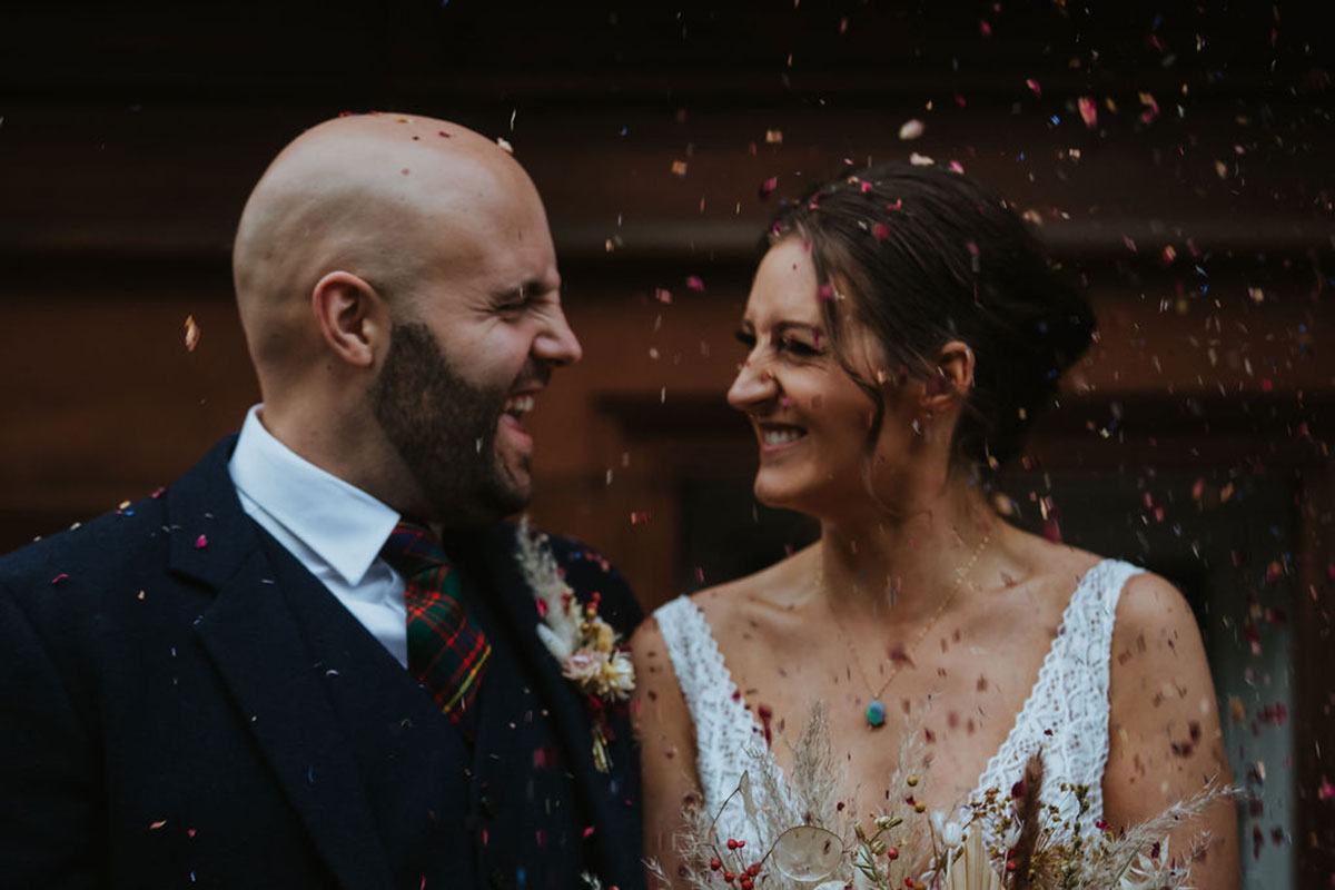 bride and groom laughing and being showered in confetti outside Waldorf Astoria Caledonian Edinburgh hotel