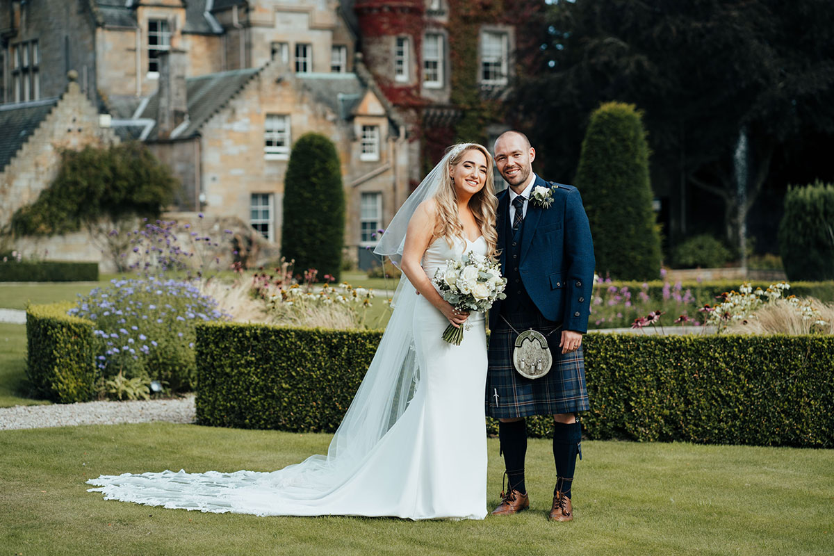 bride and groom smiling in gardens of Carlowrie Castle