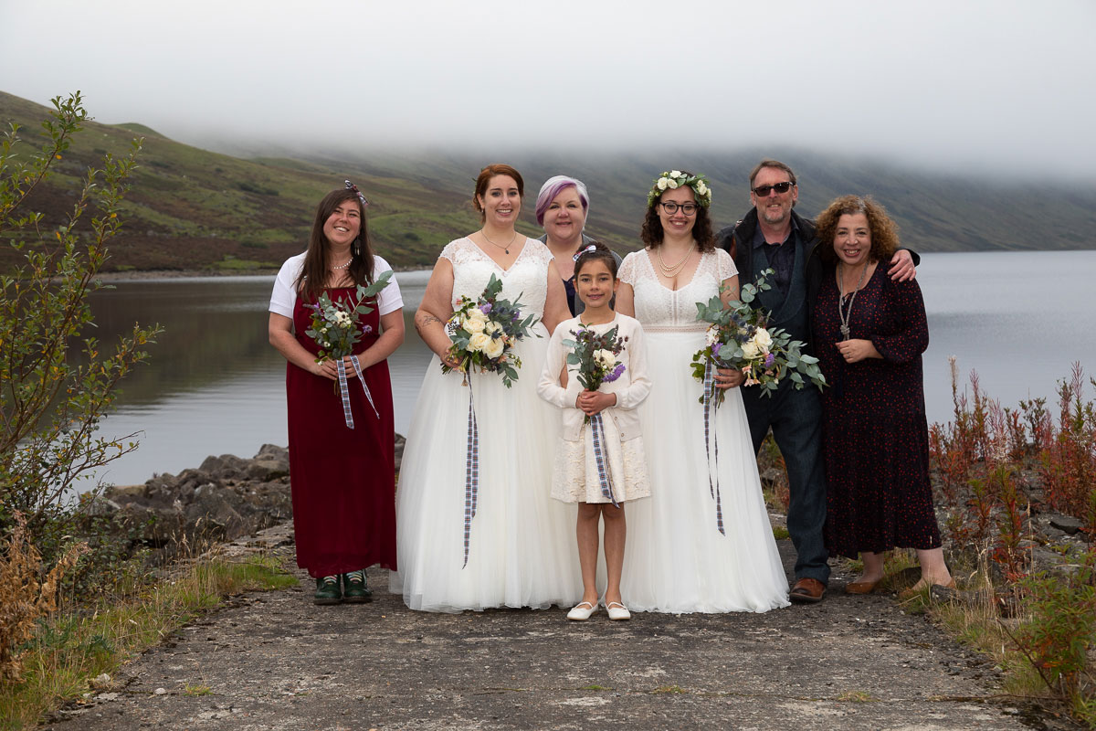 two brides pose with wedding guests after wedding ceremony on shore of Loch Turret Reservoir in Perthshire