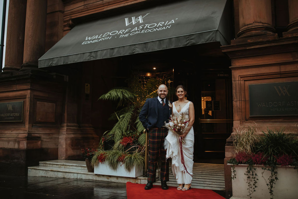 bride and groom standing outside Waldorf Astoria Caledonian Edinburgh hotel