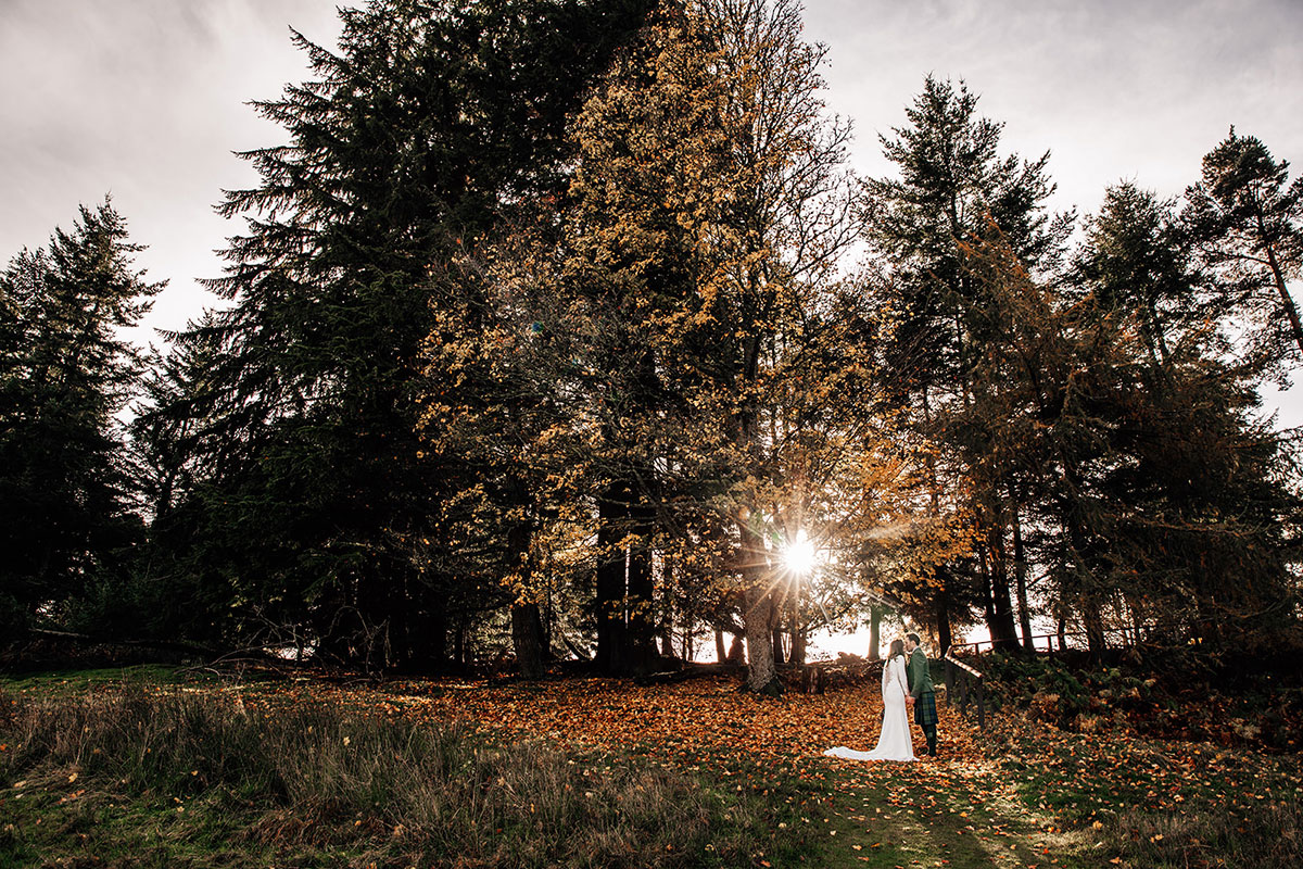 bride and groom with autumn sun shining through trees at Cardney Steading