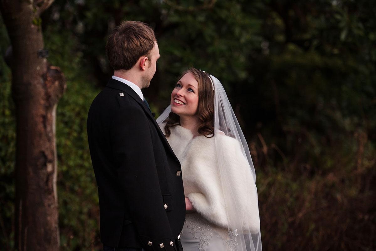 bride wearing faux fur wrap smiling at groom in Botanic Gardens in Glasgow