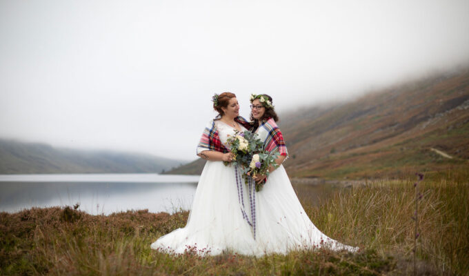 two brides wearing tartan shawl on shore of Loch Turret Reservoir in Perthshire