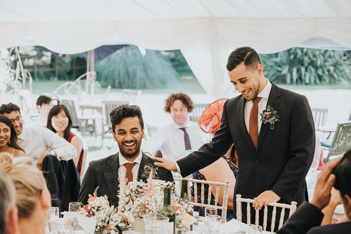 best man touching groom on shoulder and laughing during best man's speech in marquee at Balinakill Country House