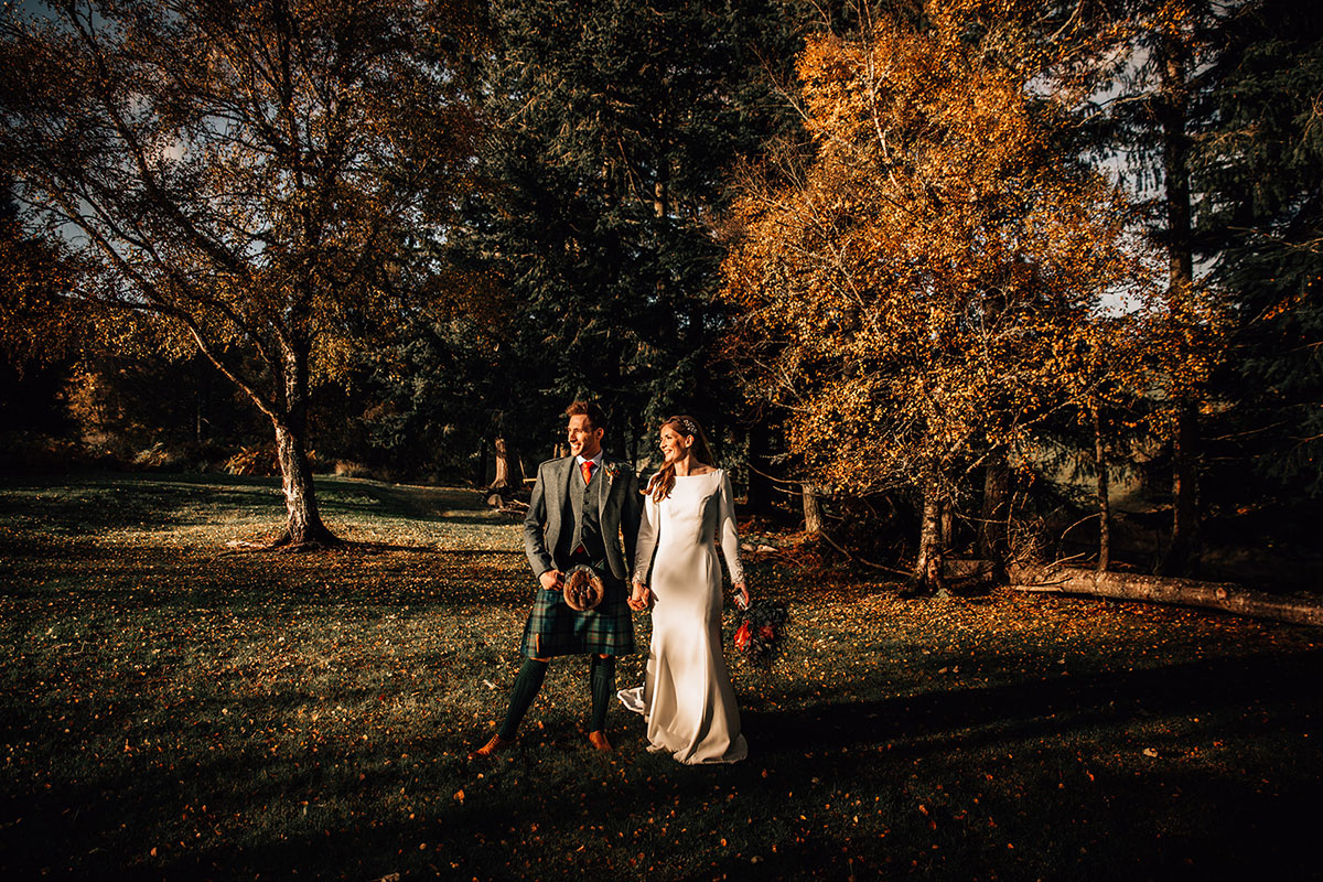 bride and groom bathing in golden autumn sunlight at Cardney Steading with trees in background