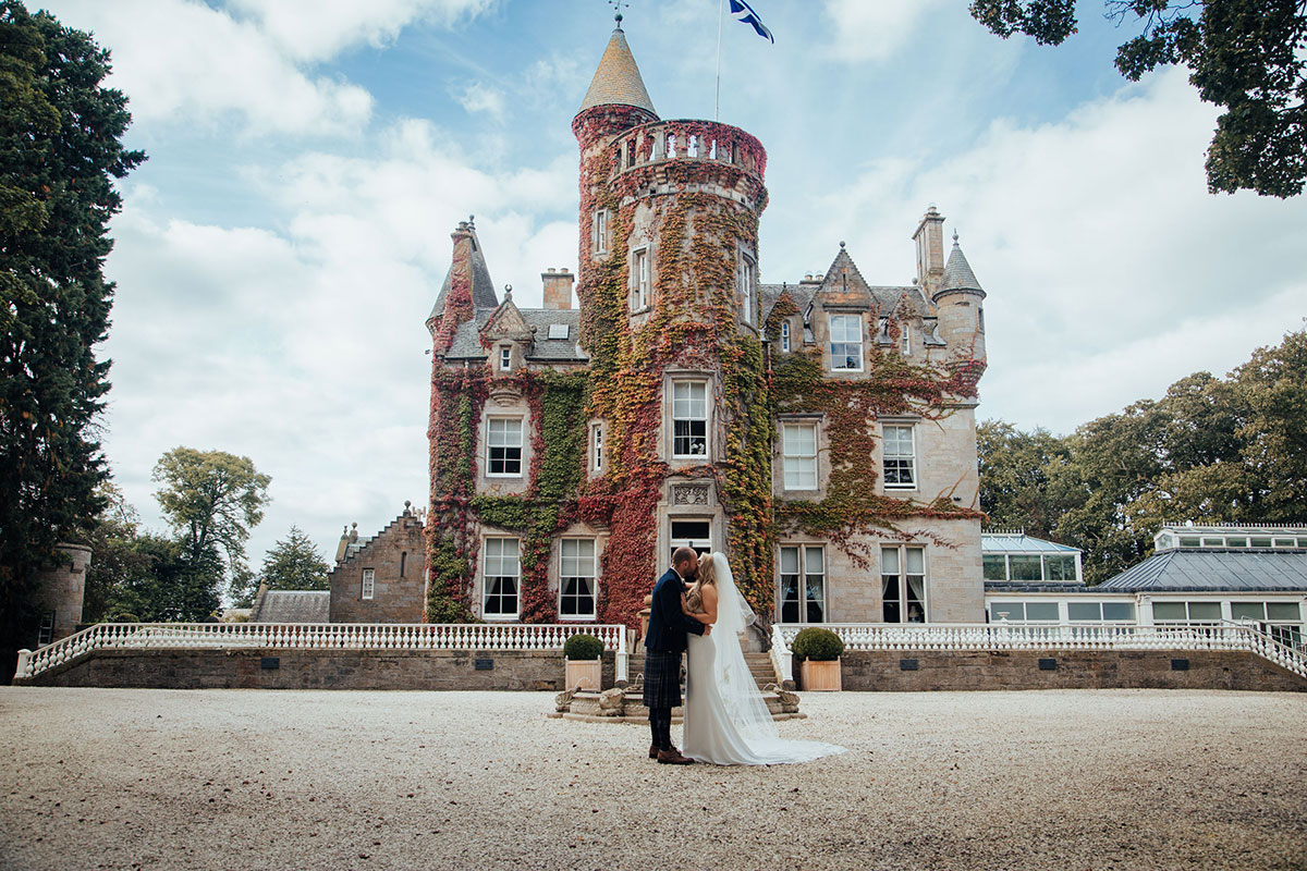 bride and groom outside ivy facade of Carlowrie Castle