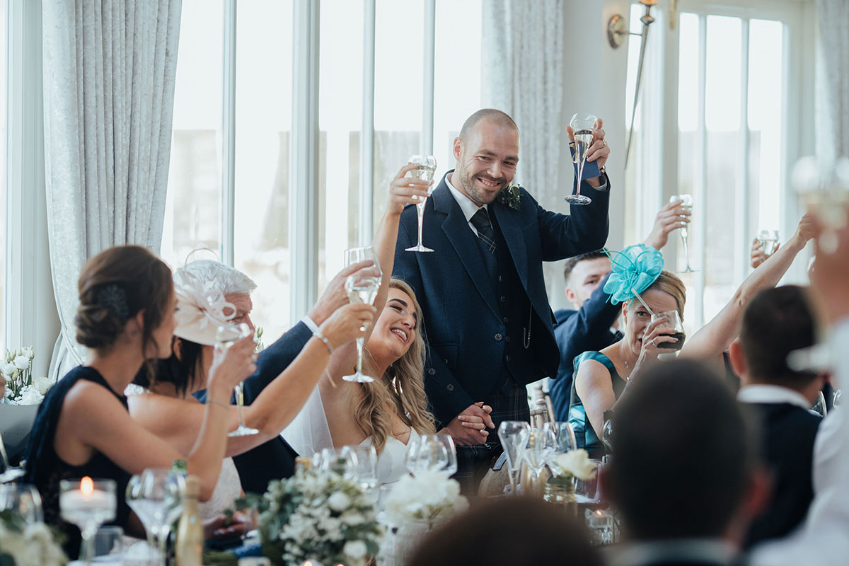 top table at Carlowrie Castle raising glasses during groom's speech