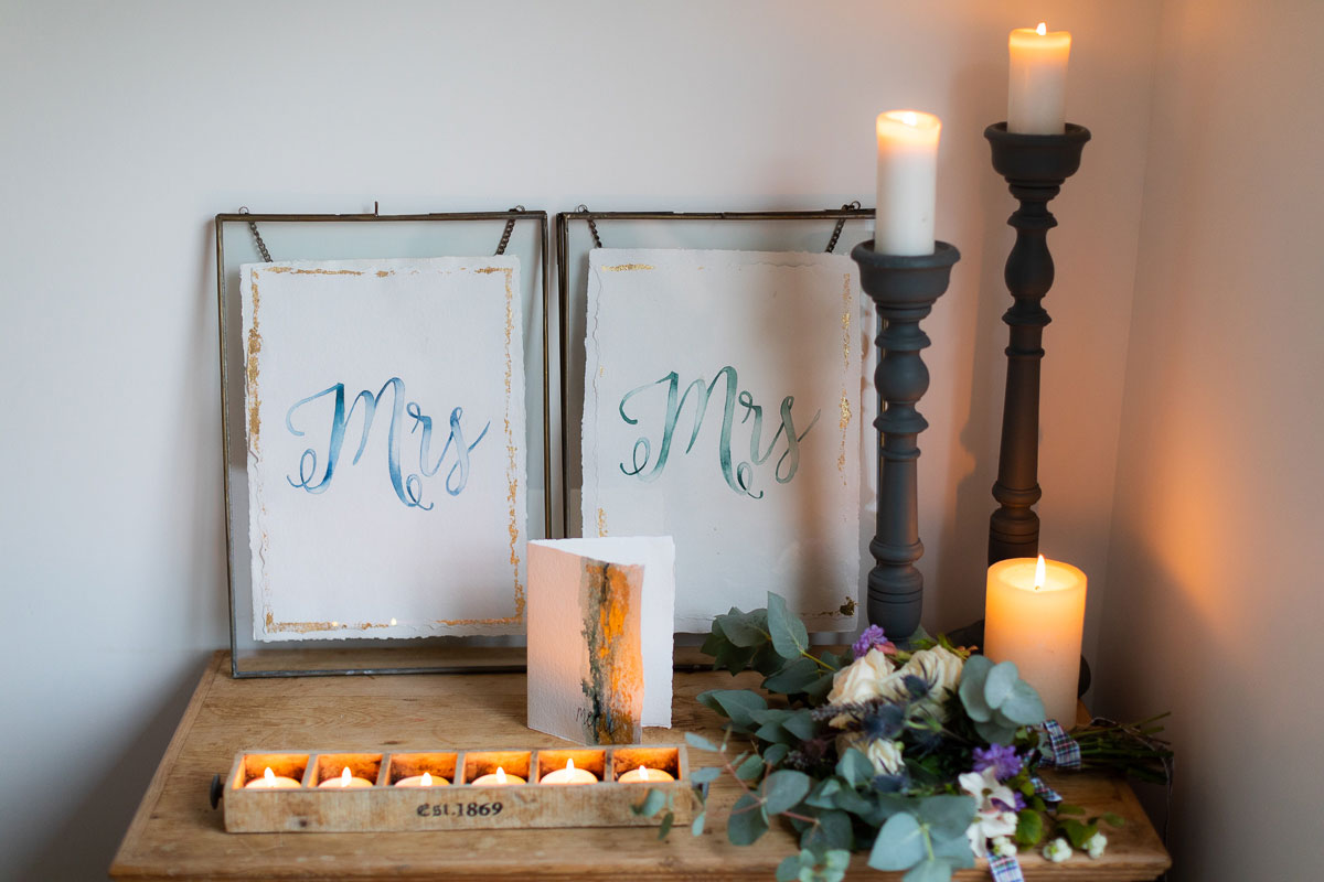 blue watercolour Mrs and Mrs wedding sign in frame with lots of candles in foreground