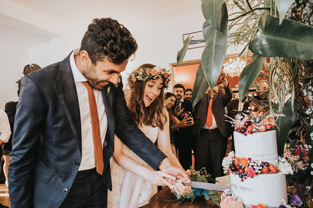 bride and groom cutting Rosewood Cakes wedding cake