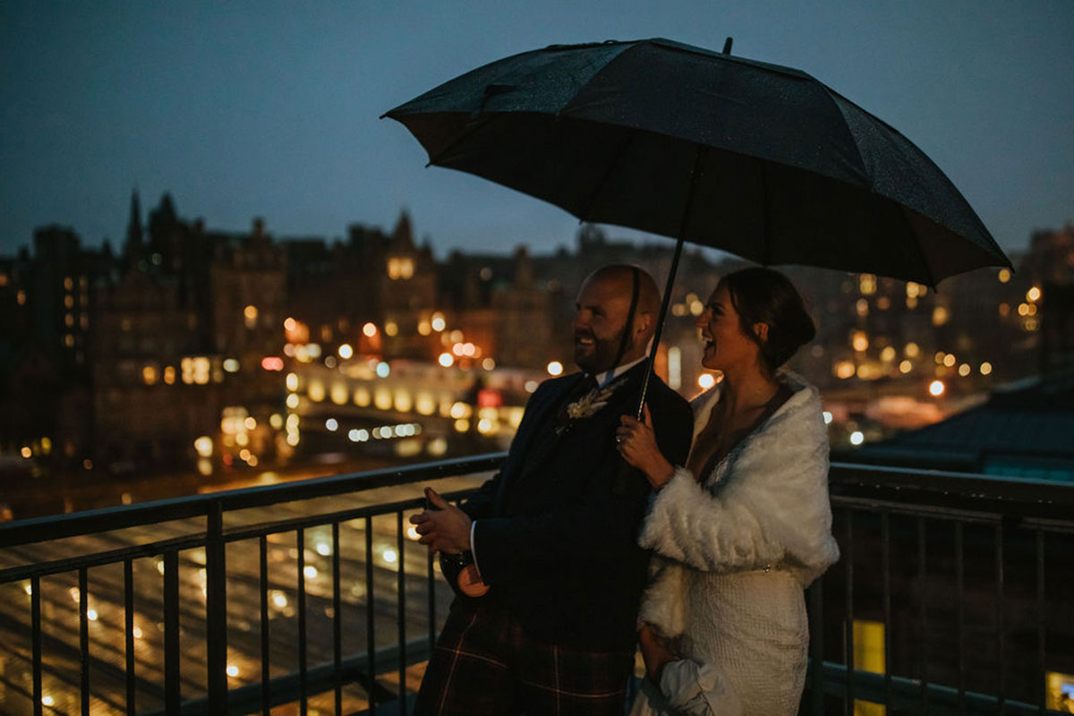 bride and groom watching Chinese lantern on balcony of Edinburgh hotel at night while holding umbrella