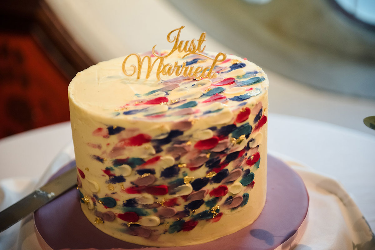 colourful stipple-effect icing on small wedding cake with Just Married gold script cake topper