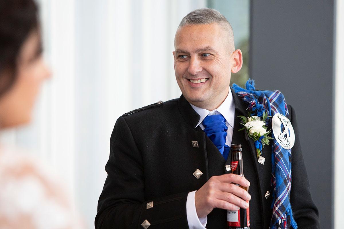 smiling groom holding bottle of beer