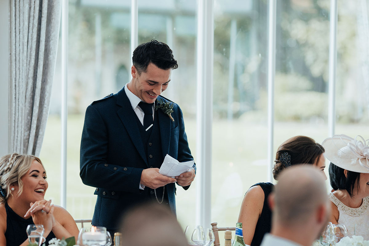 best man laughing looking at notes while making speech