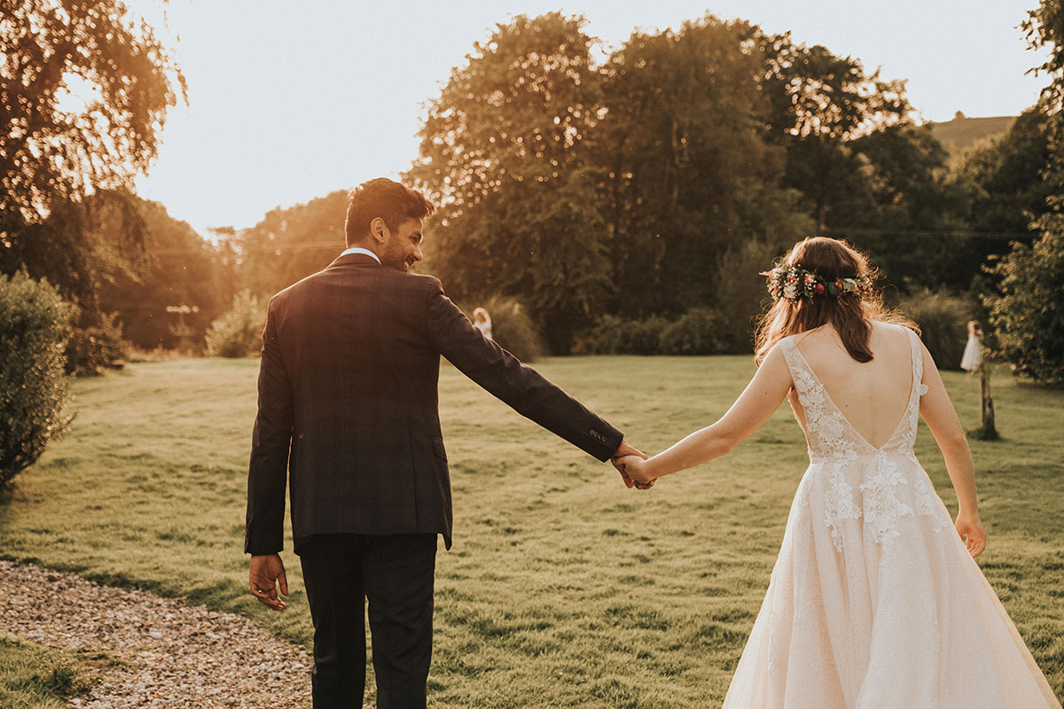 bride and groom walking hand in hand in the garden at Balinakill Country House at sunset
