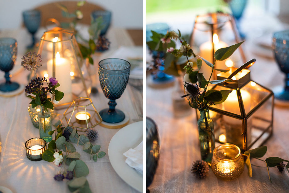 gold geometric candle lantern and blue wine glasses on dinner table set for a wedding
