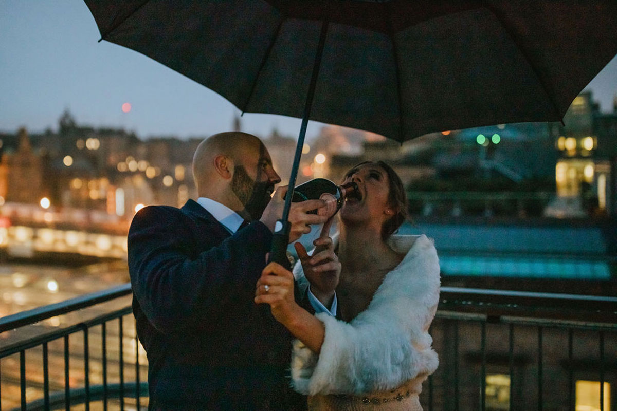 groom pouring champagne into bride's mouth on balcony of Edinburgh hotel at night