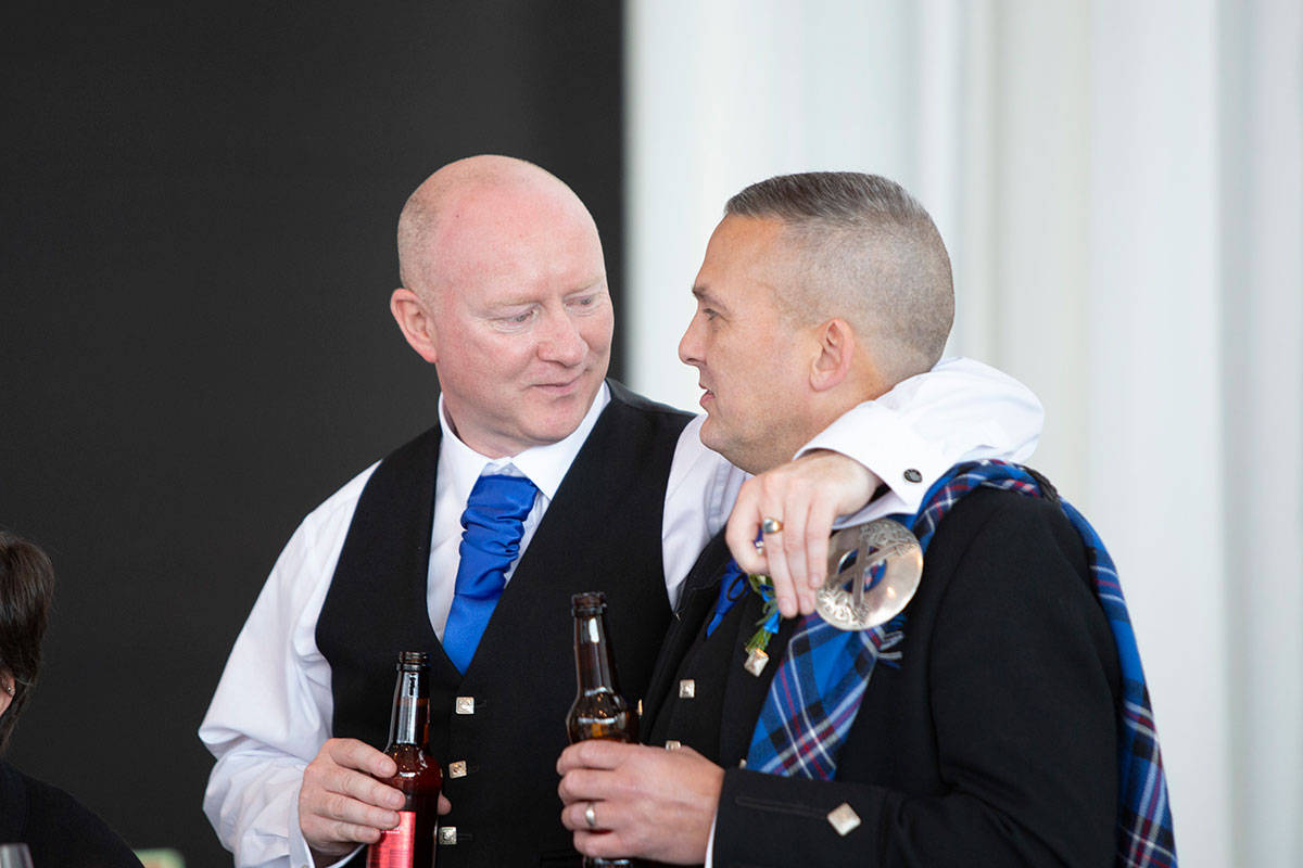groom with wedding guest drinking beers