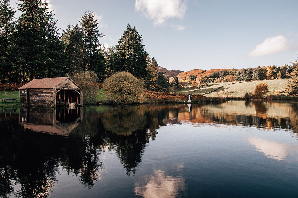 landscape of loch and boathouse at Cardney Steading with bride and groom small in background
