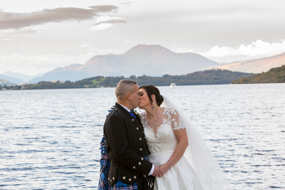 bride and groom kissing on shore of Loch Lomond with Ben Lomond in background