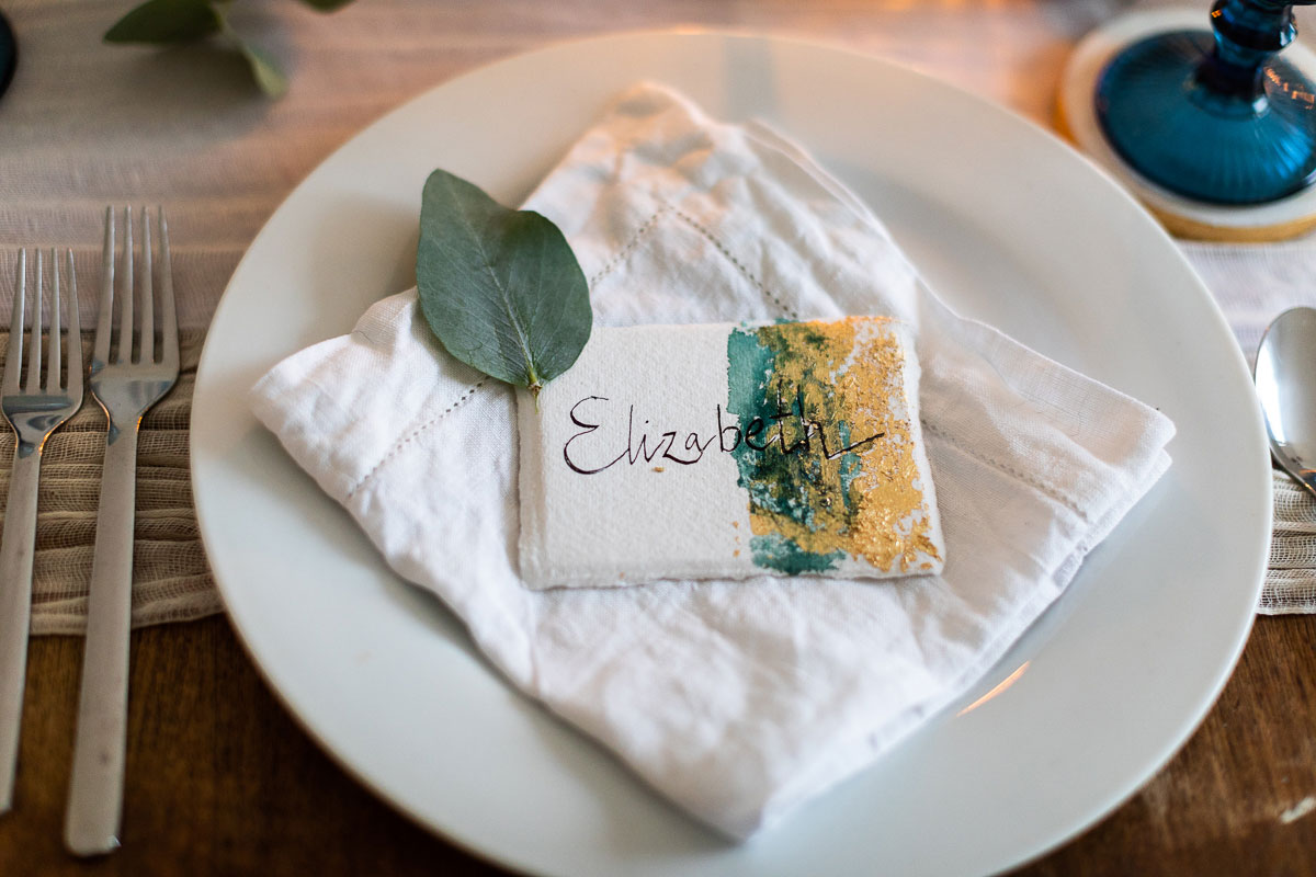 green and gold watercolour effect place setting at wedding on plate with white linen napkin and green eucalyptus leaf