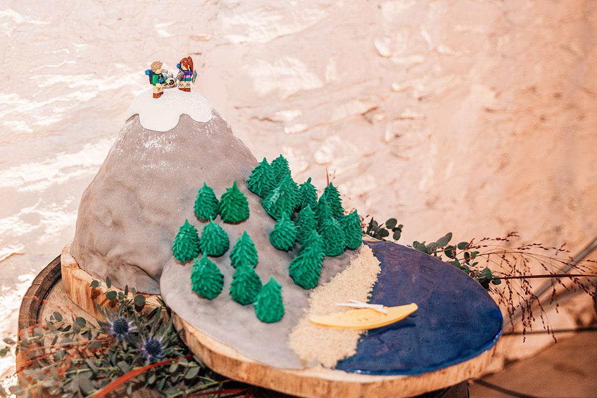 homemade French Alps ski scene wedding cake with LEGO figurine bride and groom cake topper