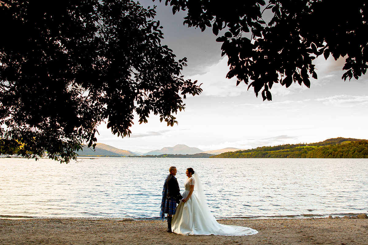 bride and groom holding hands at Loch Lomond