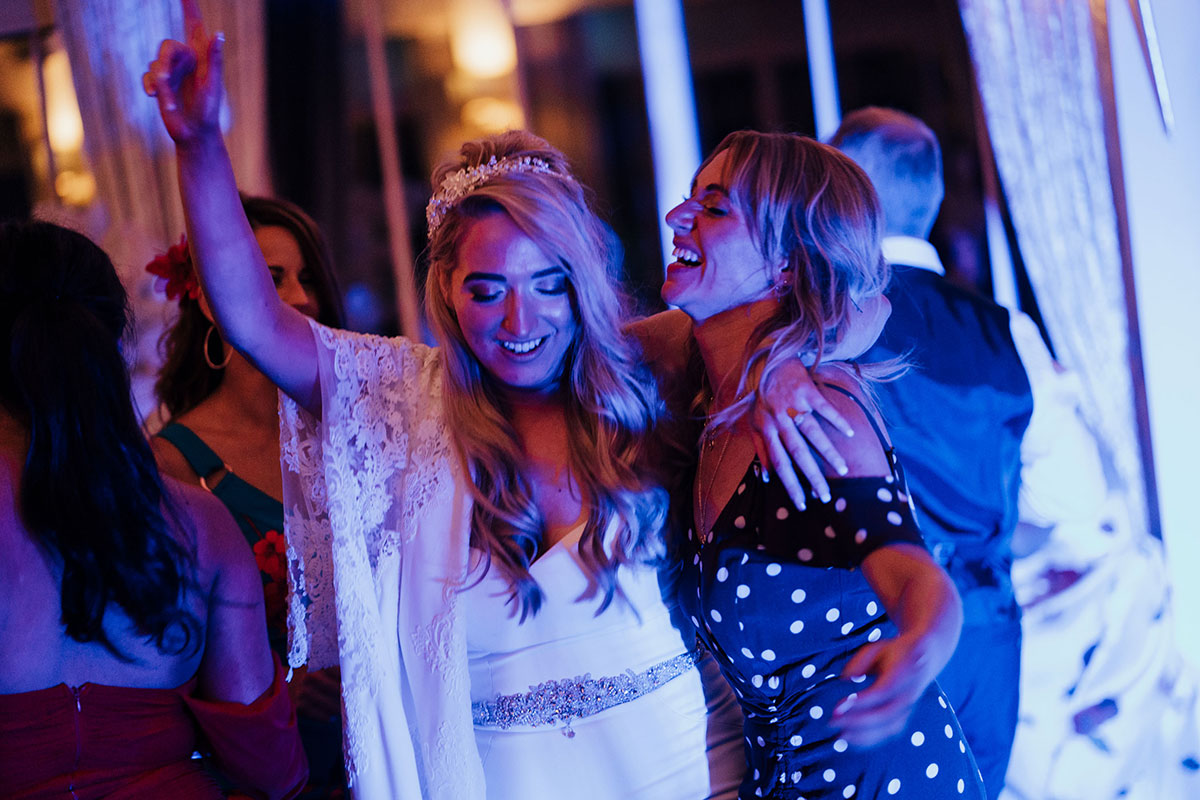 bride on dancefloor at Carlowrie Castle with arm around female wedding guest wearing polka dot dress
