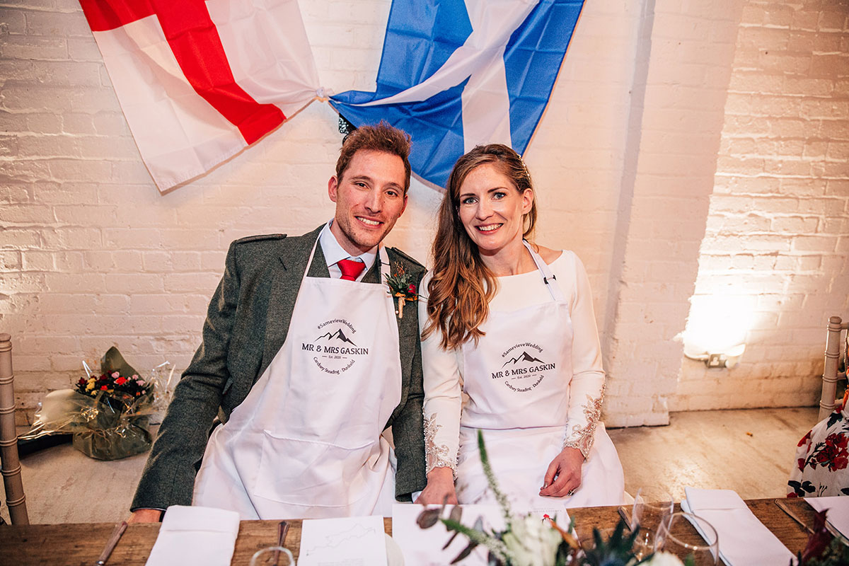 bride and groom sitting at top table wearing matching his and her aprons with Scottish and English flags in background